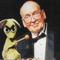 George Latshaw (1923-2006), American puppeteer, puppet builder and author, with dog glove puppet. Cover of <em>Puppetry Journal</em> (Winter 2006). Photo: Richard Termine