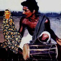 Un marionnettiste de <em>sakhi kundhei</em> manipule la marionnette à gaine de Radha, l'amoureuse de Krishna, en jouant le <em>dhol</em> et en <em>c</em>hantant les mélodies qui a<em>c</em><em>c</em>ompagnent les exploits de Radha et Krishna (<em>Or</em>issa [Odisha], en Inde). Photo réproduite avec l'aimable autorisation de Sampa Ghosh