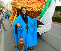 A puppeteer with a string puppet perform at a street parade, Coopérative Masrah Arous Wahran (<em>Or</em>an [Arabi<em>c</em>: <em>Wahrān</em>], Algeria). Photo: Houari Abdelkhalek
