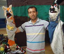 Puppeteer with two glove puppets from the puppet theatre group, Coopérative Masrah Arous Wahran (<em>Or</em>an [Arabi<em>c</em>: <em>Wahrān</em>], Algeria). Photo: Houari Abdelkhalek