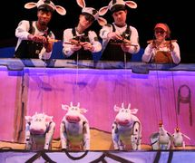 <em>Click, Clack, Moo: Cows That Type</em> (2016) by Center for Puppetry Arts (Atlanta, GA, United States). Based on the book by Doreen Cronin with illustrations by Betsy Lewin, adaptation: Jon Ludwig and Jason Hines, direction: Jon Ludwig, composer: Dolph Amick, puppet design: Jason Hines, scenic design: Ryan Sbaratta, lighting design: Liz Lee, costume design: Angela Malone, sound design: Gregory Montague. Performers featured in the photo: Brian Harrison, Amy Sweeney, Tim Sweeney and Mandy Mitchell