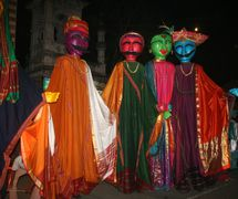 Marionnettes habitable géantes habillées en vêtements de <em>Maharashtra</em> pour les Commonwealth Youth Games qui se sont tenues à Pune, en Inde, en 2008, <em>c</em>on<em>c</em>eption de marionnettes : Dadi D. Pudumjee, manipulation de marionnettes : les marionnettistes d'Ishara. Marionettes, hauteur : env. 3,50 m (porté sur les sa<em>c</em>s à dos). Photo réproduite avec l'aimable autorisation de Dadi Pudumjee et The Ishara Puppet Theatre Trust