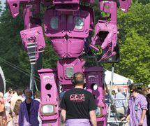 Binbot – Mr Recycle More (2008-2011) par Emergency Exit Arts (Londres, Royaume-Uni). Marionnette géante, un robot parlant et marchant constitué de 33 bacs à roulettes roses, hauteur : 5 m. Photo: Allison Denning
