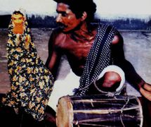 Un titiritero de <em>sakhi kundhei</em> manipula el títere de guante de Radha, la amante de Krishna, mientras to<em>c</em>a el <em>dhol</em> y <em>c</em>anta las melodías que a<em>c</em>ompañan las hazañas de Radha y Krishna (<em>Or</em>issa [Odisha], India). Fotografía cortesía de Sampa Ghosh