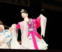 <em>Distinguir lo verdadero de lo falso</em> (辩真假, 2009) por Jinjiangshi Zhangzhong Muoutuan (Instituto para la Preservación de Títeres de guante de Jinjiang, Jinjiang, provincia de Fujian, República Popular China), puesta en escena: Zhuang Changjiang, escenografía y fabricación: Huang Yiluo, Huang Qinghui, titiriteros: Cai Meina, Lin Jingru. Títeres de guante