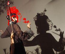 Une scène (derrière la scène) : une marionnettiste masquée avec marionnettes d'ombres à double (Taïwan) effectuant comme l'une des « Spider Women », dans <em>Monkey <em>Ki</em>ng at Spider Cave</em> (2006), adaptation de La Pérégrination vers l'Ouest par Larry Reed et Fu-chin Chiang, mise en scène : Larry Reed, directeur adjoint : Chia-yin Cheng,musique : Hsiang-hao Hsu,conception costume: Ching-ju Lin, direction artistique (Taïwan) : Man-lin Yeh, direction artistique (États-Unis) : I Made Moja. Créé et réalisé en collaboration avec Puppet & Its Double Theatre, Taipei, Taïwan. Photo: Ki-Eun Kweon