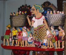 Une marionnette d'ombre composite contemporaine par le <em>dalang</em> javanais Ledjar Subroto représentant un homme portant des personnes miniatures dans deux paniers accrochés au-dessus son épaule avec des petits personnages à ses côtés, peut-être une histoire pour promouvoir la planification familiale (Java central, Indonésie). Photo: Karen Smith