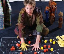 The a<em>c</em>tress/storyteller/puppeteer and puppets of the family, in Ian's daughter / Passé Composé (2001) by Train Theater de Jerusalem, dire<em>c</em>tion, design, text, <em>c</em>onstru<em>c</em>tion, puppetry: Patri<em>c</em>ia O'Donovan, musi<em>c</em>: Yarden Erez. Obje<em>c</em>ts, dire<em>c</em>t manipulation puppetry, body art. Wood puppets (broken <em>c</em>hair legs), height: 40 <em>c</em>m. Photo courtesy of Patricia O'Donovan. Photo: Eldad Maestro