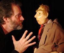 Rod Burnett y el Man in the Overcoat (el Hombre del abrigo), en <em>The Half Chick</em> (1995), por Storybox Theatre (Bristol, Reino Unido), puesta en escena: Tanya Landman, concepción y fabricación de títeres: Rod Burnett, actor en la foto: Rod Burnett. Títere de mesa, altura: 1,0 m. Foto: Rod Burnett