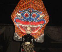Semar, un títere de varillas del <em><em>wayang</em> golek <em>Sunda</em></em> que aparece delante del lado de la otra cara de la figura de la sombra del <em>kayon</em> (<em>gunungan</em>) que representa la cara de Kala. Foto: Karen Smith