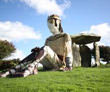 Bendigeidfran (Brân le Béni) assis contre la chambre funéraire mégalithique de Pentre Ifan (North Pembrokshire, Pays de Galles), dans <em>The <em>Healing of Brân / Iachau Bendigeidfran</em></em> (2010) par Small World Theatre (Cardigan, Pays de Galles, Royaume-Uni). Marionnette géante animée par des acteurs, hauteur: 7,60 m. Un spectacle épique en plein air basé sur le folklore gallois et les contes, Tales of the Mabinogion, réalisé en gallois et en anglais, avec des marionnettes géantes, des acteurs sur des tricycles géants et un bateau, des artistes de rue, des chorales locales, et avec la participation de la communauté. Photo: Sam Vicary