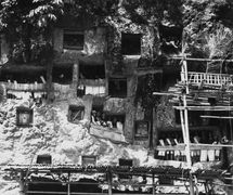 Tombs carved into the rock face near the village of Lemo, Tana Toraja, Indonesia, with several <em>tau-tau</em> guarding at tomb entrance (1971). Photo courtesy of Collection: Tropenmuseum (Amsterdam, the Netherlands)