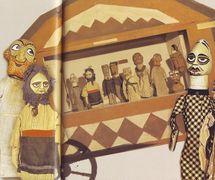 """Boîte-théâtre en bois portable et des marottes de """"Revolyutsiynyy vertep"""" (<em>Vertep</em> révolutionnaire, 1923-1924), le théâtre de marionnettes d'agitation soviétique de l'É<em>c</em>ole d'art et de <em>c</em>éramique Mezhygirsky (région de Kyiv). Texte, mise en s<em>c</em>ène, <em>c</em>on<em>c</em>eption et <em>c</em>onstru<em>c</em>tion de marionnettes, manipulation : les étudiants du <em>c</em>ollège (sous la dire<em>c</em>tion artistique de Pavel Gorbenko). Les personnages du jeu, <em>Svyato v rayu</em> (Va<em>c</em>an<em>c</em>es au paradis), et les <em>c</em>roquis politiques des étudiants du <em>c</em>ollège (premier plan) : Saint, Femme (Baba), Prêtres ; (arrière-plan) : les mêmes personnages et deux politi<em>c</em>iens en fra<em>c</em>s. Colle<em>c</em>tion : Musée d'Etat de Théâtre, Musique et Cinéma d'Ukraine (<em>Ki</em>ev)"""